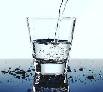 decorativa, un vaso de agua en post sobre medicina ambiental para sugerir que ingerimos tóxicos con la comida y bebida